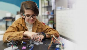 concentrated-elementary-girl-assembling-circuit-6ZB2PVL